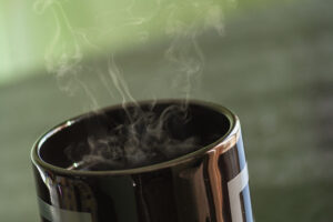 Black cup of coffe with steam rising from it.