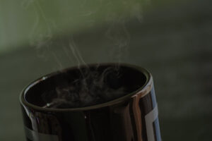 Black cup of coffee with steam rising from within it.